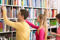 Three students looking for books and standing in a row in a library.